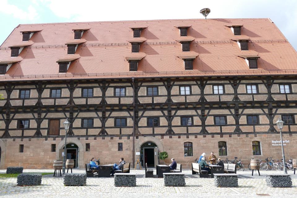 Unser Museum HopfenBierGut in der Aussenansicht mit Sitzplätzen und Beschattung